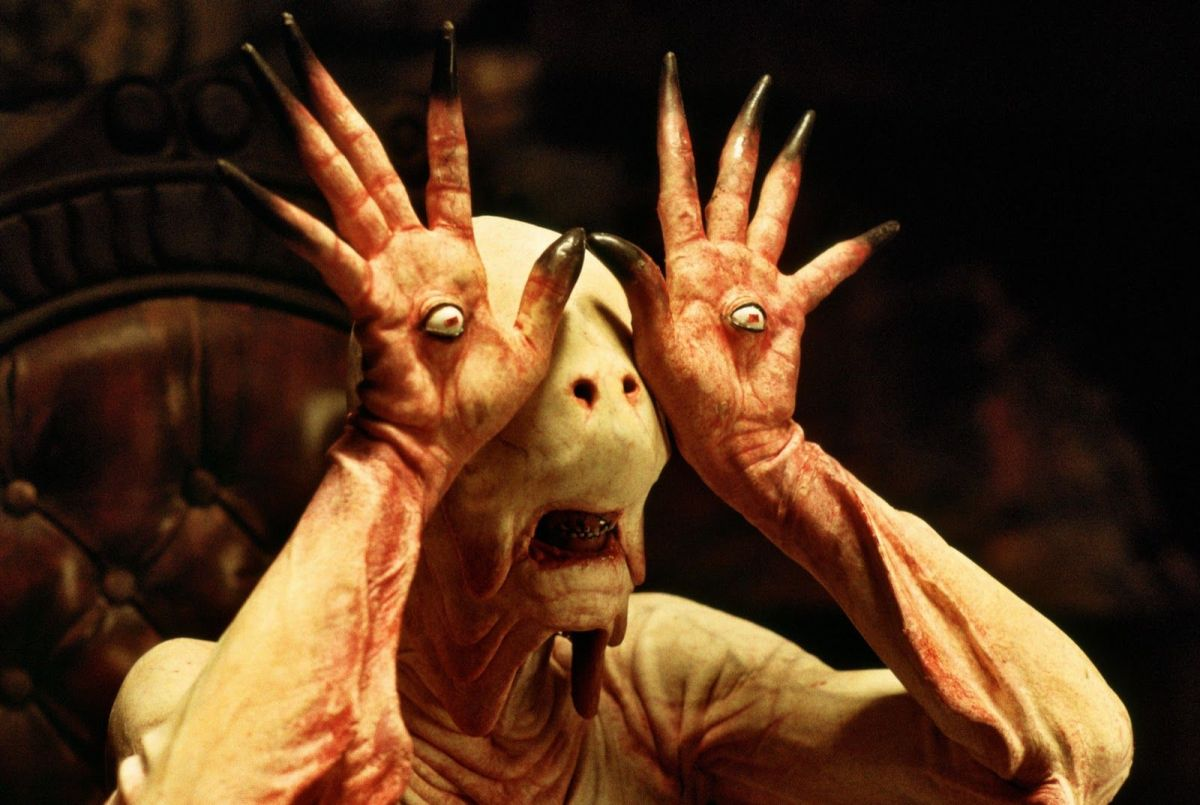 The Pale Man looking around the room with his eyes in his hands.