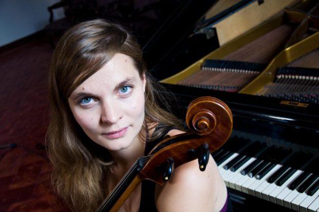 Hildur Guðnadóttir with her cello in front of a piano.
