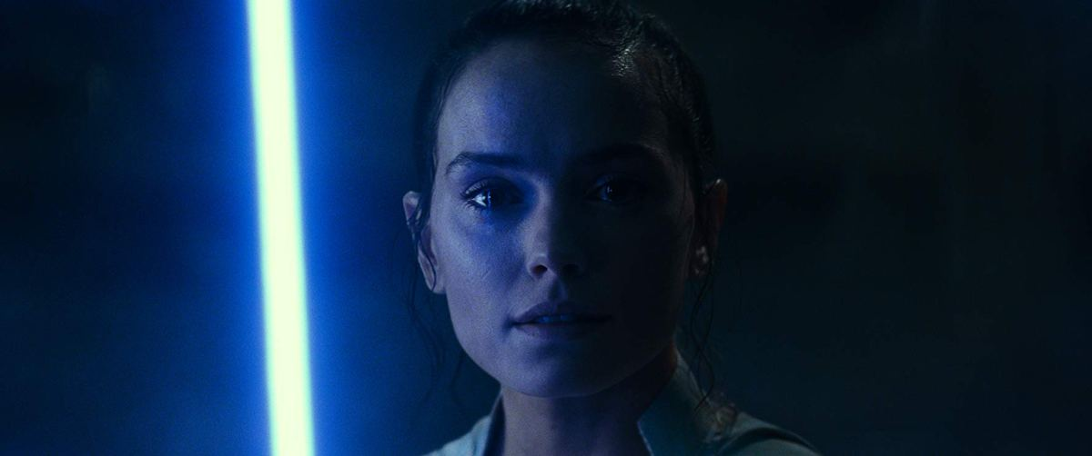 Rey stands in darkness with Luke's blue lightsaber
