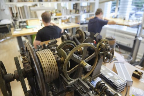 The steam-punk machinery in the foreground is a rare rose engine that engraves straight-line as well as circular patterns. The fashion for engine-turned dials has put these antique machines in demand and they are increasingly hard to come by.