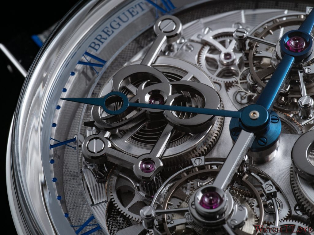 Two tourbillons mounted on a revolving main plate hand-engraved on a rose engine.
