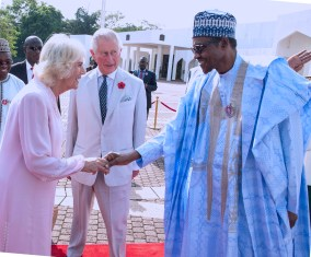 President Buhari in a handshake with Duchess of Cornwall, Camilla, while Prince Charles looks with interest
