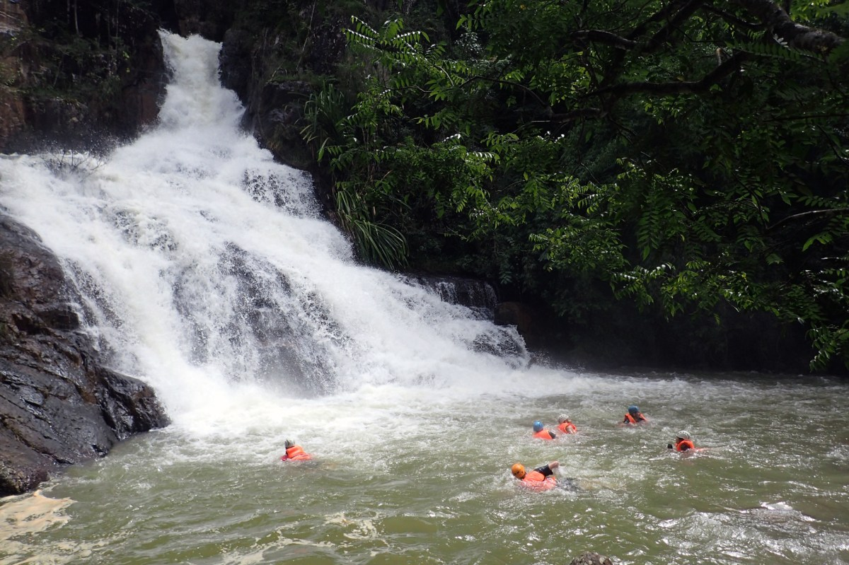 People on a canyoning tour cool off by swimming near a waterfall