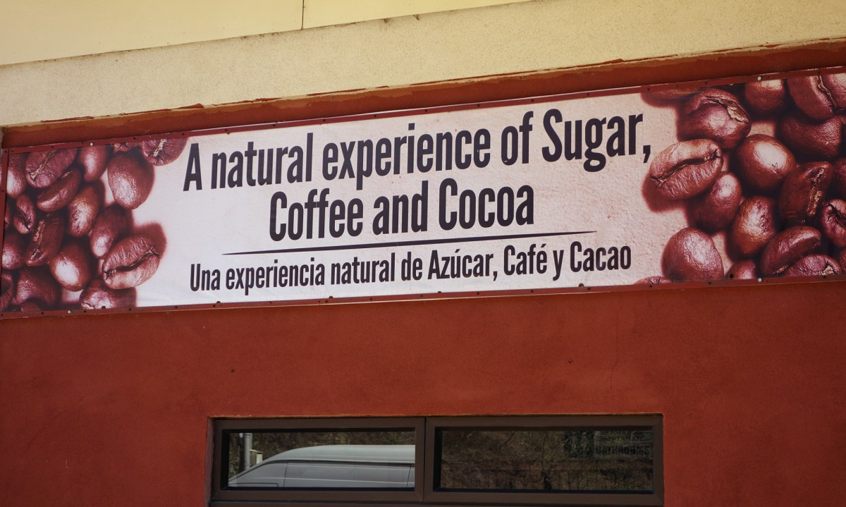 a natural experience of sugar coffee and cocoa sign in front of the tour
