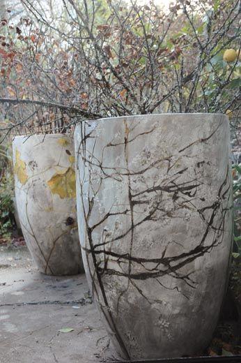 Empreintes de branches et feuilles sur des grands pots en béton