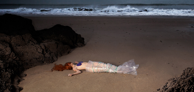 Une femme emballée façon petite sirène, morte sur une plage