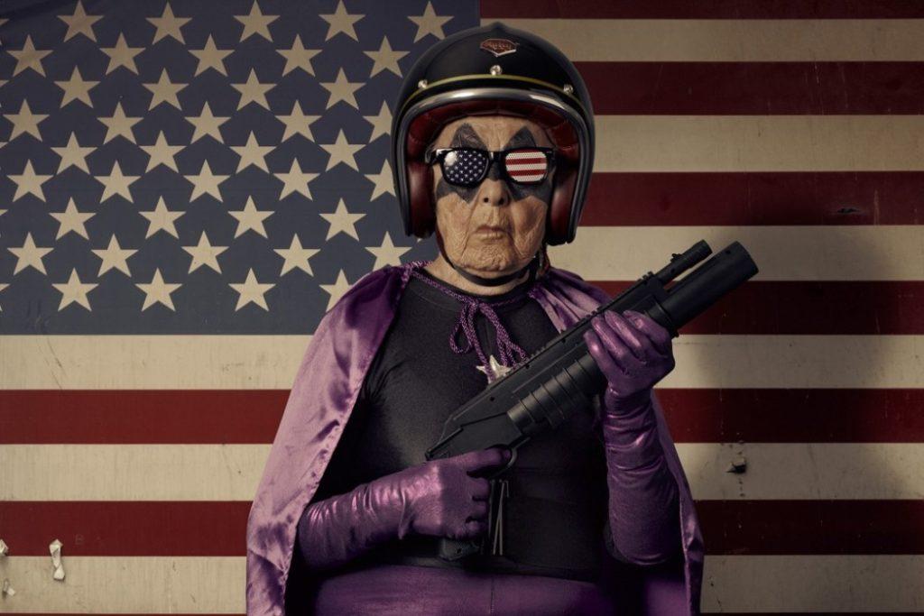 Grand-mère Mamika avec une cape et une arme sur fond de drapeau américain