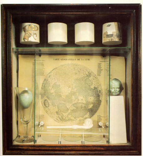 A wooden box containing a wine glass, an egg, a bubble pipe, a map of the moon, and other objects.