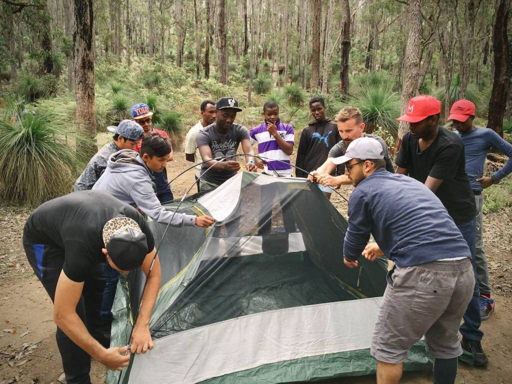 Why You Should Get Out And Give Back, Brooke Nolan, Photo First Hike, erecting a tent, team effort, onlookers, camping, trees, forest