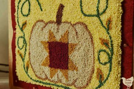 close up of two images of a punch needle embroidered pumpkin with a burgundy and gold star surrounded by green vines with gold leaves