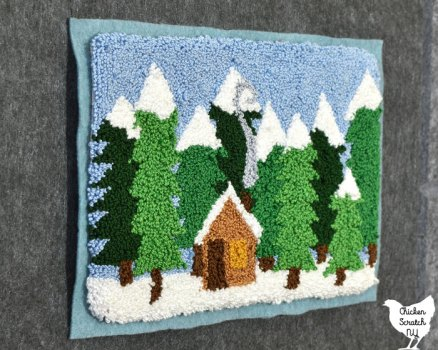 side view of winter punch needle cabin in the woods pattern