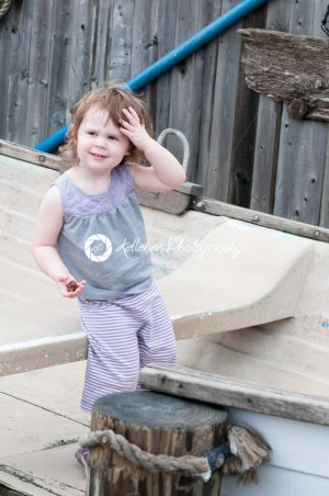 An adorable girl happily sitting in a small row boat next to mooring posts - Kelleher Photography Store