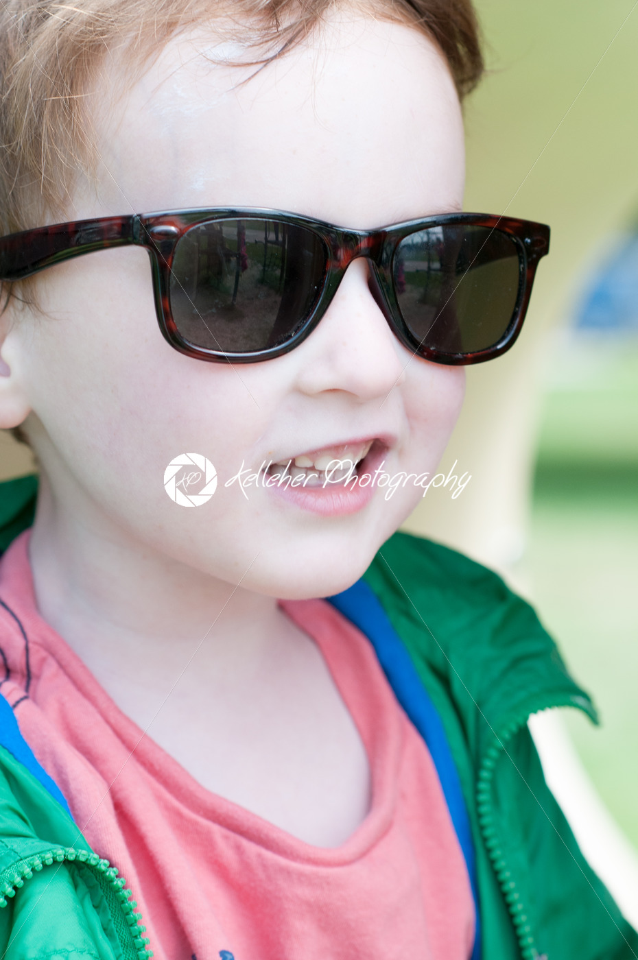 Happy little boy is swinging on see-saw wearing oversized sunglasses - Kelleher Photography Store