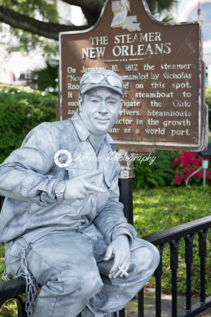 NEW ORLEANS, LA – APRIL 13: Street actor dressed up as a tin man in front of the Steamer historical sign on April 13, 2014 - Kelleher Photography Store