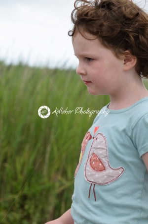 Profile of young girl walking outside along beach sand dunes with reeds - Kelleher Photography Store