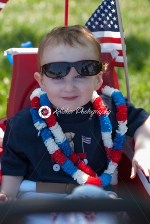 Young boy riding in red wagon having fun in the park for July Fourth - Kelleher Photography Store