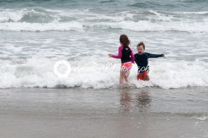Young cute little boy and girl playing at the seaside running into the surf on a sandy beach in summer sunshine - Kelleher Photography Store