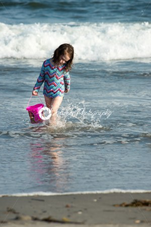 Young cute little girl playing at the seaside carrying a red bucket at the edge of the surf on a sandy beach in summer sunshine - Kelleher Photography Store