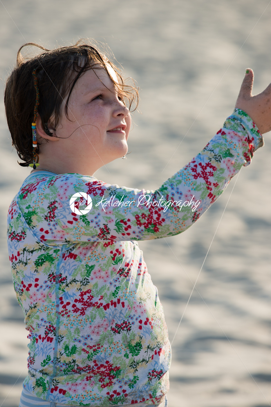 Young girl on beach with kite smiling - Kelleher Photography Store