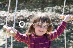 Young girl outside in backyard having fun on a swing - Kelleher Photography Store