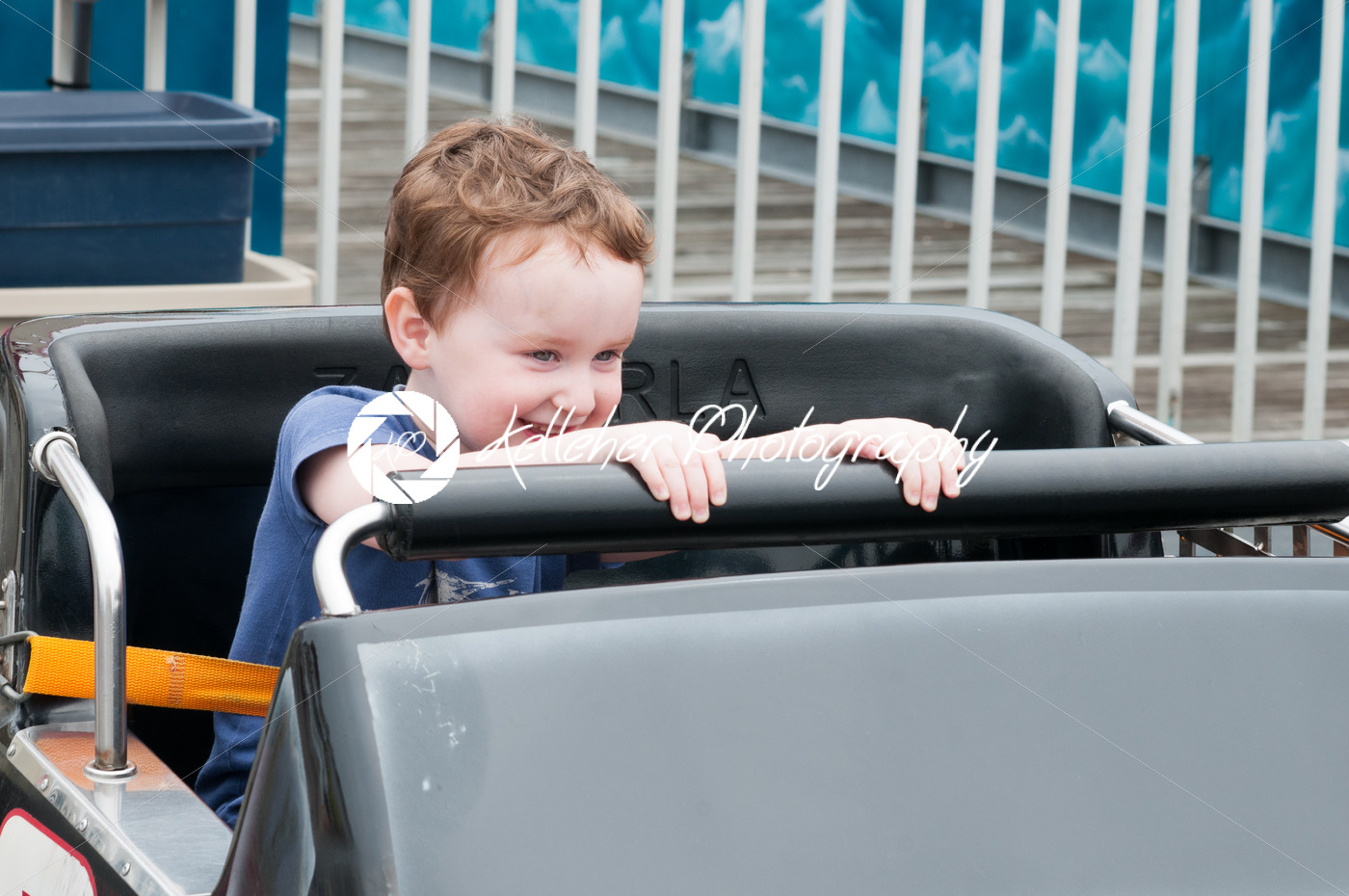 Young toddler boy having fun on boardwalk amusement ride - Kelleher Photography Store