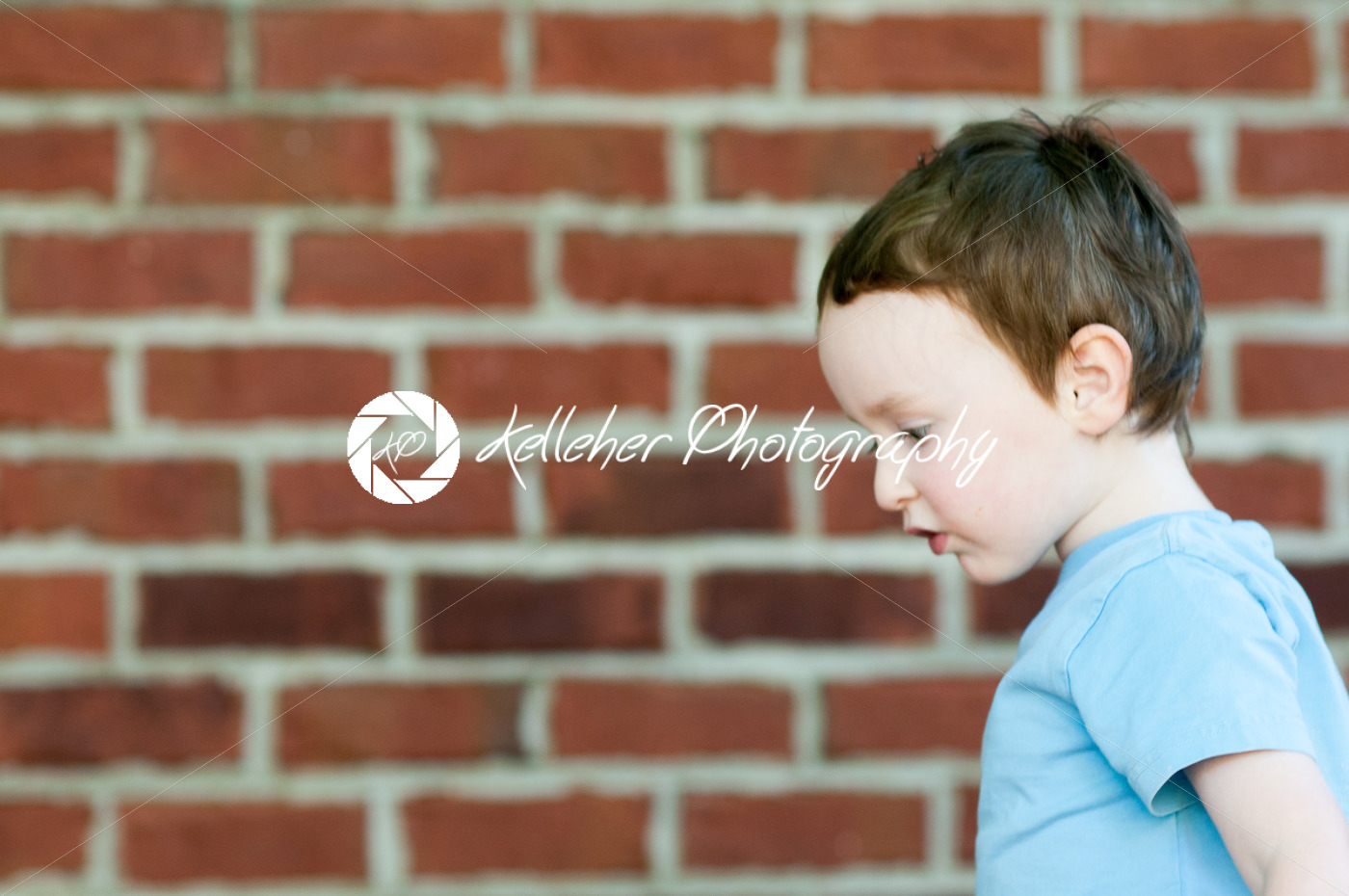 Young toddler boy in front of red birck wall - Kelleher Photography Store