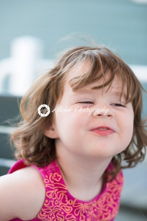 squinting expression little girl sitting down making funny face - Kelleher Photography Store
