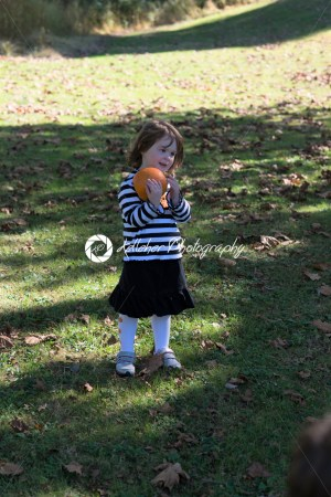 Beautiful smiling toddler girl wearing black and white Halloween outfit outdoors holding little pumpkin and smiling with grass and falling leaves in background - Kelleher Photography Store