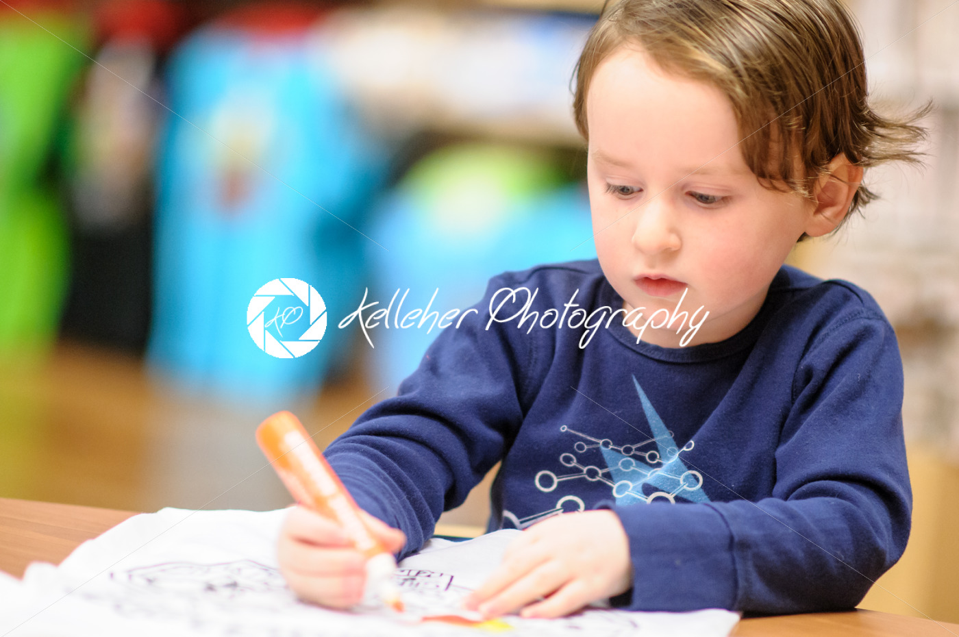 Young boy sitting down at desk indoors coloring with markers - Kelleher Photography Store