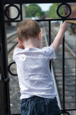 Young boy standing at back of train looking down at track - Kelleher Photography Store