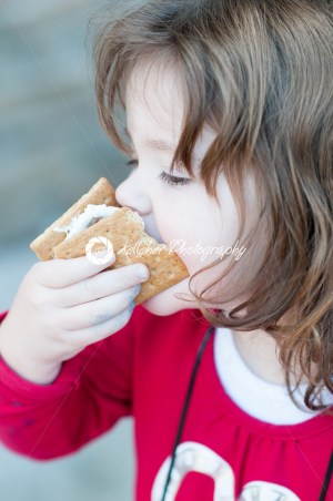 Young little girl is eating a s'more made from graham crackers, roasted marshmallows and chocolate. Her mouth is messy and she is taking a toothy bite of the s'more. - Kelleher Photography Store