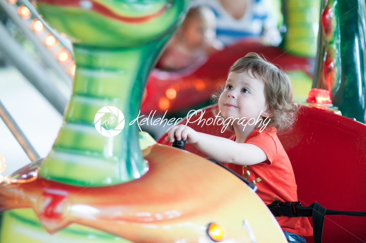 Young toddler girl having fun on boardwalk amusement ride - Kelleher Photography Store