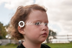 Young girl outside looking over at pumpkin fields - Kelleher Photography Store