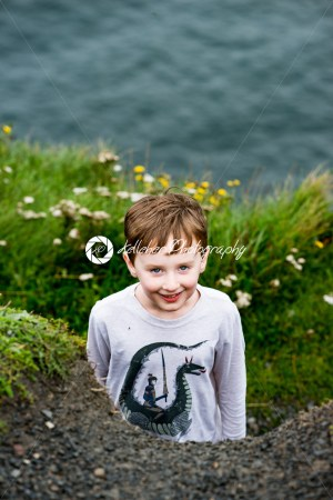 Boy looking up the Cliffs of Moher Tourist Attraction in Ireland - Kelleher Photography Store
