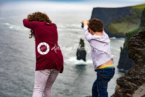 Girl and Boy pretending to dive off the Cliffs of Moher Tourist Attraction in Ireland - Kelleher Photography Store
