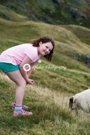 Girl looking at sheep grazing while walking up the Slieve League Cliffs, County Donegal, Ireland - Kelleher Photography Store