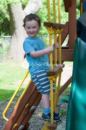Happy little child boy climbing on the rope ladder outside - Kelleher Photography Store