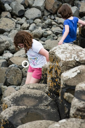 Siblings climbing the rocks at Giant's Causeway - Kelleher Photography Store