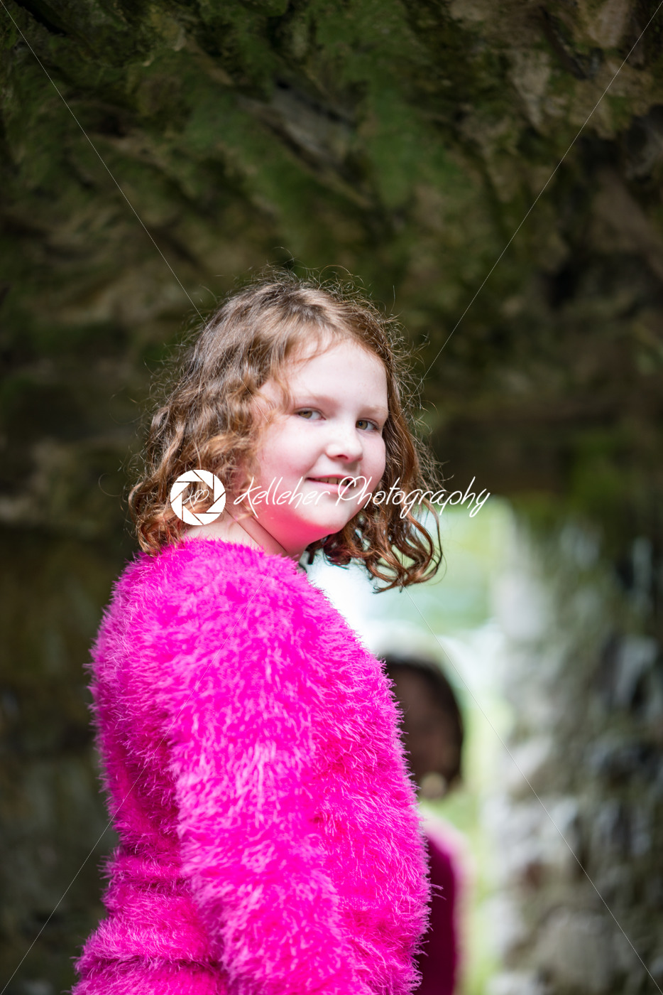 Young little girl portrait looking and smiling at the camera while exploring in an old castle - Kelleher Photography Store