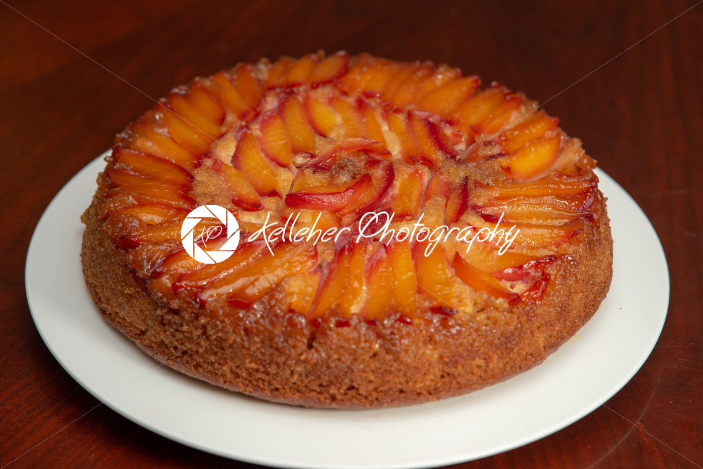 Cake with nectarines on white plate on top of dining table - Kelleher Photography Store