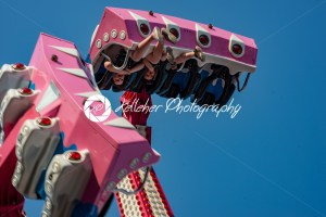 Happy young brother and sister having fun on boardwalk amusement ride - Kelleher Photography Store