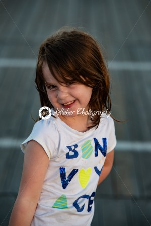 Young cute little girl on the boardwalk looking at camera smiling - Kelleher Photography Store
