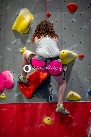 Young girl climbing up on practice wall in indoor rock gym - Kelleher Photography Store