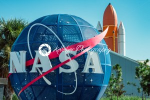 Cape Canaveral, Florida – August 13, 2018: NASA globe with space shuttle booster rocket in backgrond at NASA Kennedy Space Center - Kelleher Photography Store