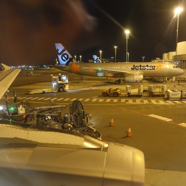 A Jetstar Airbus A320 and refueling pump viewed from out of the aircraft window