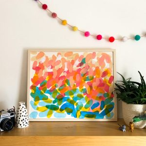 A multi coloured Rachel Hawkes Cameron painting on top of a shelf leaning on the wall beneath a wreath of colourful minature pom-pom's