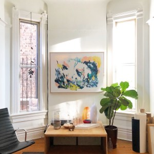 A blue and yellow Rachel Hawkes Cameron painting hanging on a white wall next to two large windows