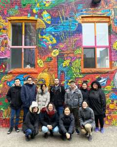 AXS Biomedical Animation Studio crouching in front of graffiti alley wall in toronto's downtown core