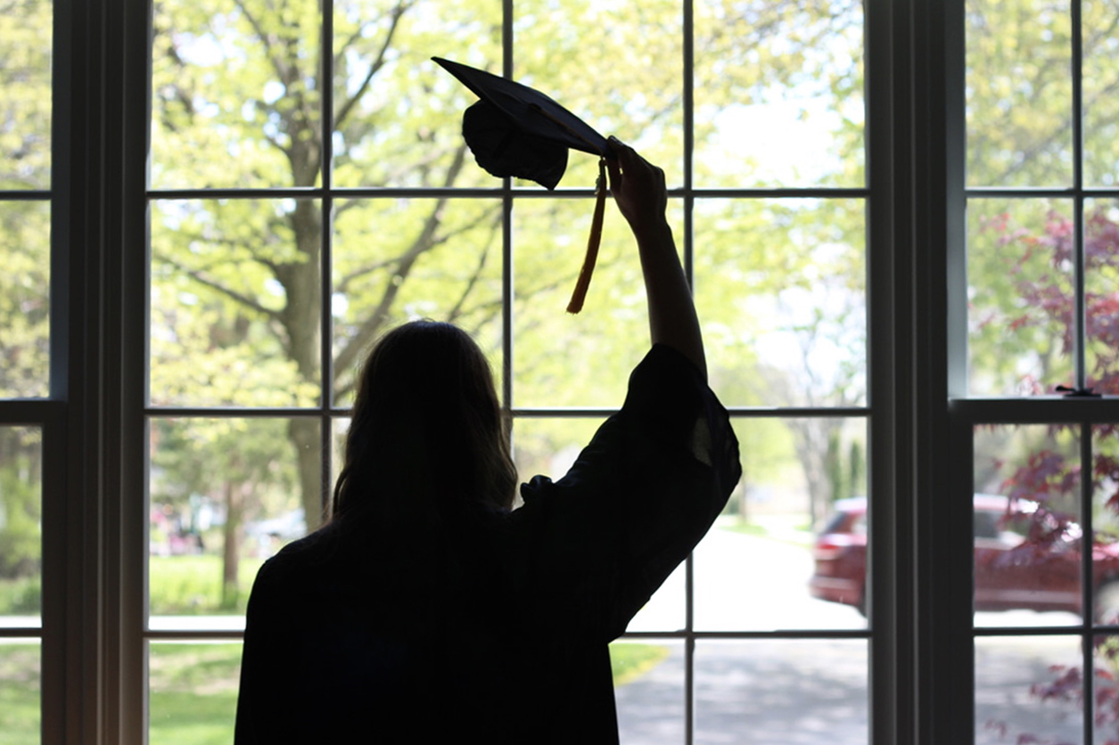 High school graduate removes her cap while staring out at the neighborhood, watching a car pass by during a virtual graduation ceremony.
