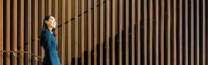 Woman in suit walking down stairs in a corporate setting with feature wall made of panelled walnut wood